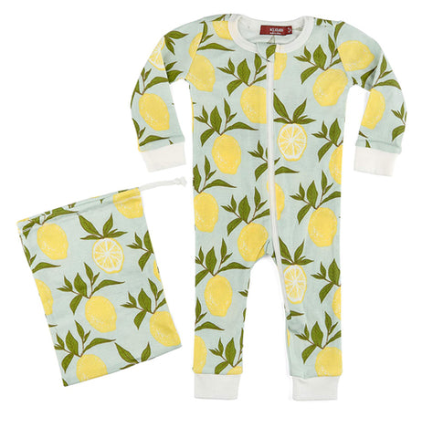 These light blue pajamas have a zipper on the front and are designed with yellow lemons that have green leafy stems from top to bottom. Next to the pajamas to the left is a pouch with the same design as the pajamas.
