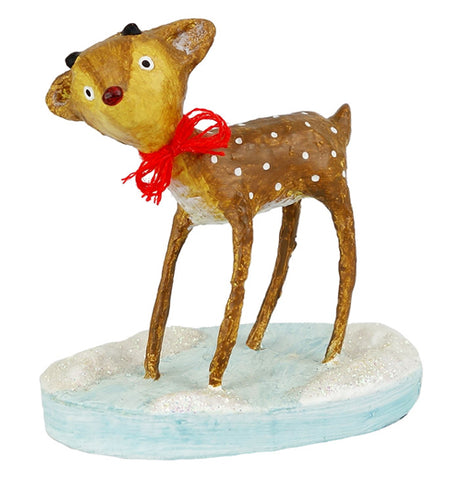 A brown and white speckled reindeer wearing a red bow on a round icy blue base