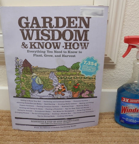 The book featuring Gardening Wisdom and Know-How is shown sitting on a rug next to a windex spray can.