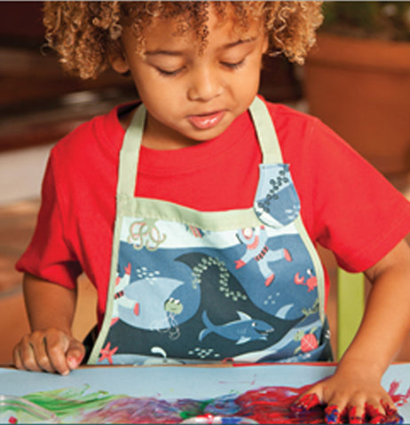 A child in a red shirt is shown wearing the ocean apron.