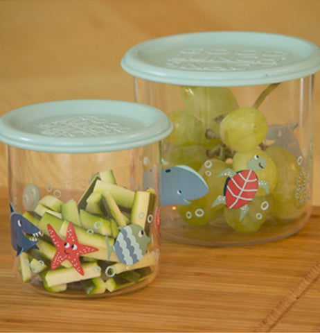 Two clear snack containers with Ocean themed sea life in red and different shades of blue sitting on a wood counter. One has green grapes in it, the other has cut up zucchini sticks. Each snack containers has a light blue lid attached.