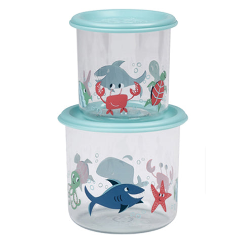 Two different sized clear plastic containers stacked on top of each other, the smaller on top. Each has a light blue lid and silhouettes of sea life such as sharks, starfish, octopus and crabs in red and different shades of blue. To the right is the top view of a container in the packaging.