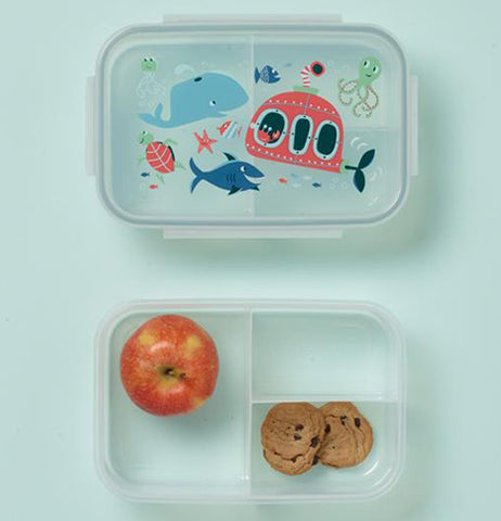The container's lid wit the ocean design is shown at the top of the image. The container at the bottom of the image is shown with an apple and two cookies.
