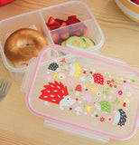 The lunch box with the porcupine design lid is shown with a bagel and some fruit inside it.