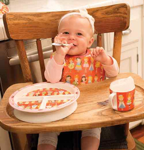 A baby is shown wearing the princess bib with a plate and cup of a similar design on the high chair.