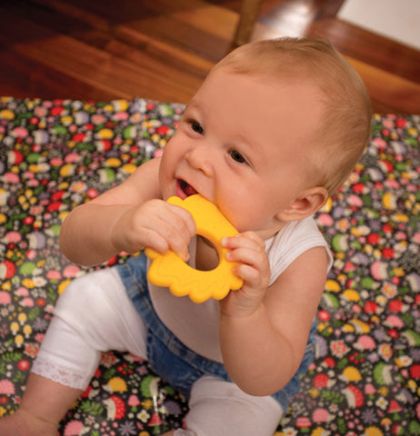 "A baby seeking his teeth on the yellow Silicone ""Hedgehog"" Teether."