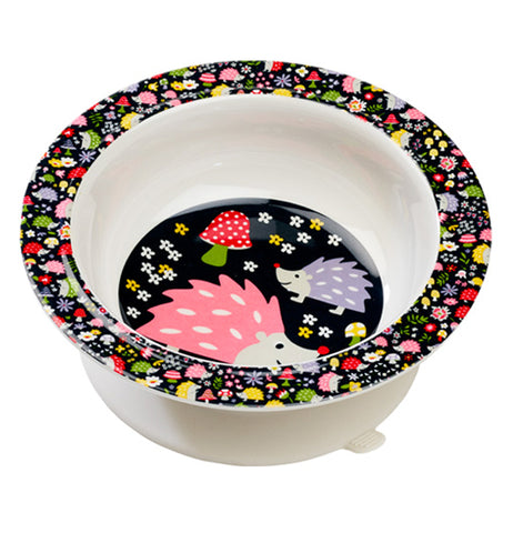This white bowl with a black rim and bottom features a design of yellow, red, periwinkle, and green flowers on its rim, and a pink and periwinkle hedgehog pair on the bottom standing in front of a red and green mushroom.