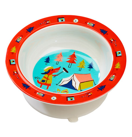 A bowl is seen from a downward angle. The rim is red, and has small designs on it like trees, compasses, and lanterns. The sides of the bowl are white. The bottom of it has an anthropomorphic red dog with black ears wearing a light brown top and roasting a hot dog over a campfire. To the right of the dog, there is a tent. There are five trees in the background.