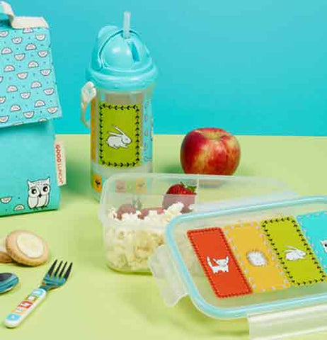 Bento box laying on a table with a sippy cup, an apple, and a lunch sack.