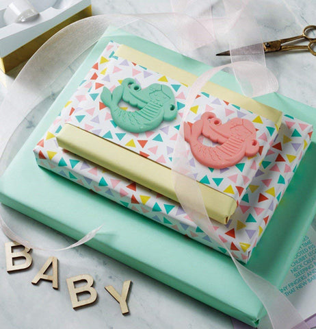 Both colored, teal and salmon pink colored teether, sit on a polka dot patterned paper wrapped around a teal green box.