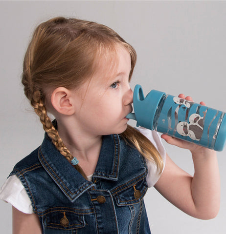 A little girl in a blue coat and pigtails is shown drinking from the blue water bottle.