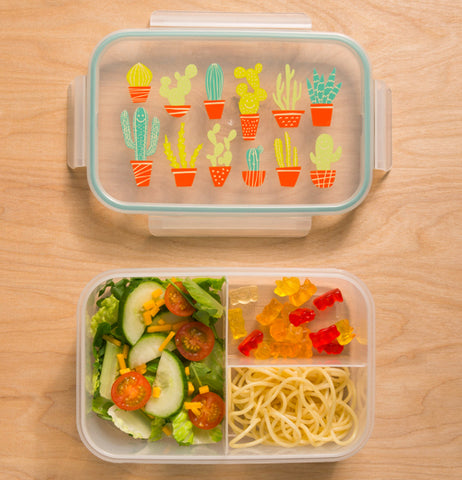 The lunch box with the cactuses on its lid is shown with some vegetables, noodles, and gummy bears in it.