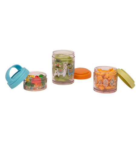 The three containers are sitting open. The smallest is a clear container that has banners of flags around it with gummy bears. the next container that shows llamas showing kiwi slices in the container. the last container is holding goldfish and has a triangular pattern.