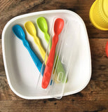 The set of four Infant Spoons were set in the bowl on the table. The red spoon sits in the open clear case.