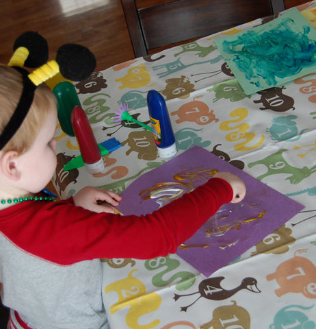A little boy is shown doing artwork using the numbered animal splat mat as cover for the table.