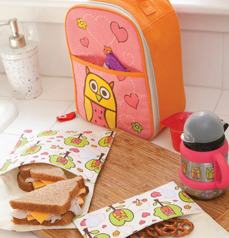 The pink and orange lunch box with the owl and hearts on it is shown sitting on a table in front of some bags with a sandwich and some pretzels. A matching cup on the right of the lunch box is shown.