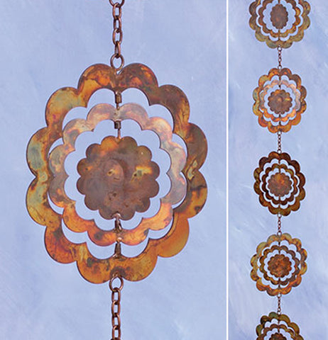 The image on the left shows a single bronze metal sunflower shape against a blue background. The image to the right shows the five golden metal sunflower shapes, also against the blue background.