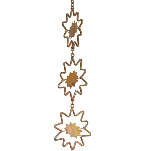 Close up view of a sunburst rain chain in gold and copper colors.