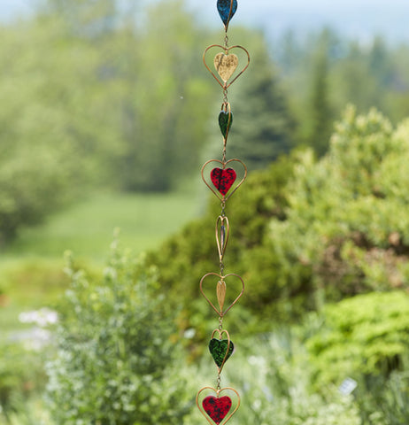 Yellow, green, red and blue  hearts on a chain hanging outside.