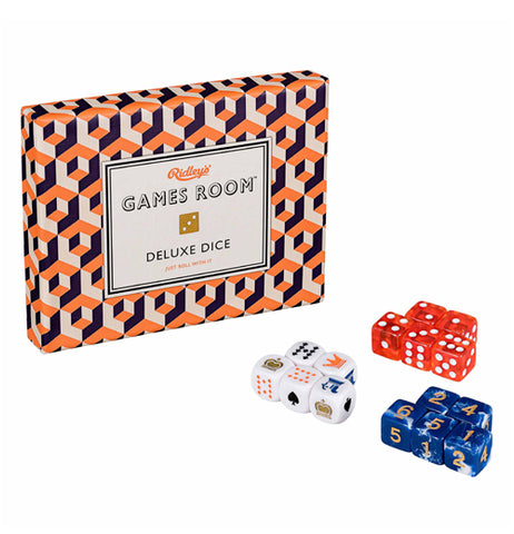 The box with the orange, white, and black checkered pattern is shown with its die contents on display. At the top are the red and white dice. Below them, to the right, are the blue and yellow dice. The white dice with the playing card symbols are shown to the left of the blue and yellow dice.