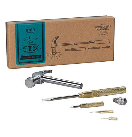 "This multi-tool Is pulled apart to show the detached hammer head and the handle with a flathead screwdriver bit inserted laying next to The screwdrivers bits. Behind them sits a box with a blue sticker with the words, ""Hit it For Six""."