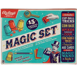 "This magic kit box show the contents of the kit: small red balls under cups, a yellow and black wand, and a few different colored magic playing cards. It also shows a stage magician in a top hat waving a wand. The words, ""Magic Set"" are shown in black lettering across the middle of the box."