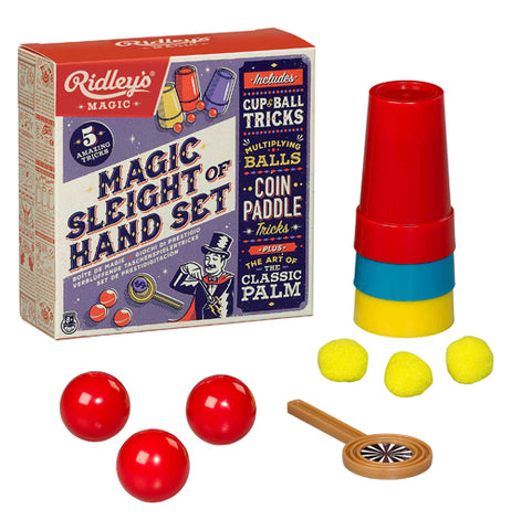 The purple and black box holding the magic kit is shown with a few of its contents on display. A red cup, blue cup, and yellow cup are shown to the right. Below the cups are three yellow balls. Below those balls is a coin paddle. Next to the magnifying glass to the left are three red balls.