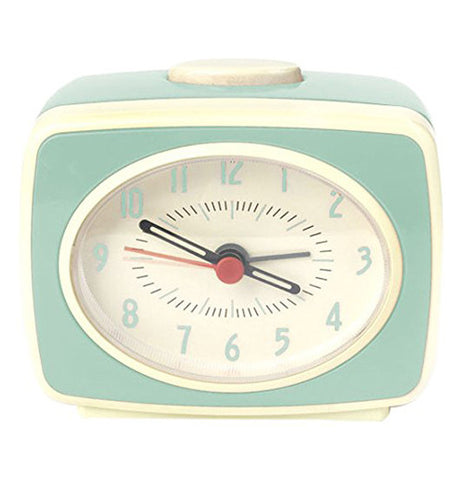 Mint green retro alarm clock with a white snooze button on top.