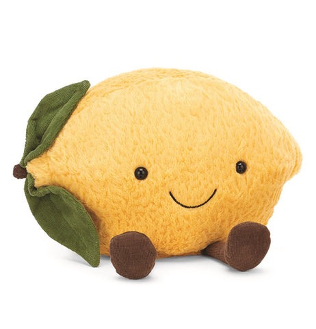 Smiling plush lemon with green leaves on the side and brown feet sticking out on a white background.