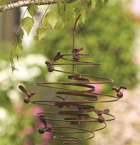 "This Double Spiral ""Bees"" Garden Hanger hands on a tree limb outside the garden."