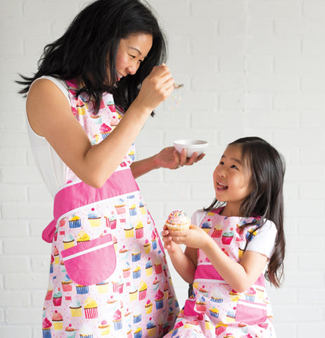 A mother and daughter are both shown wearing the pink aprons with the different colored cupcakes covering them.