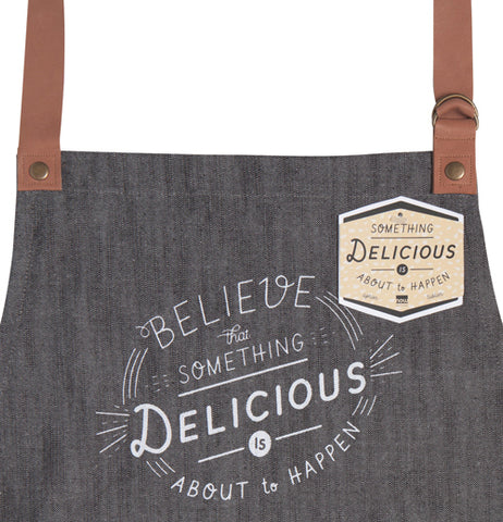 "The close-up of the ""Something Delicious"" Apron has a tag on it with two brown straps."