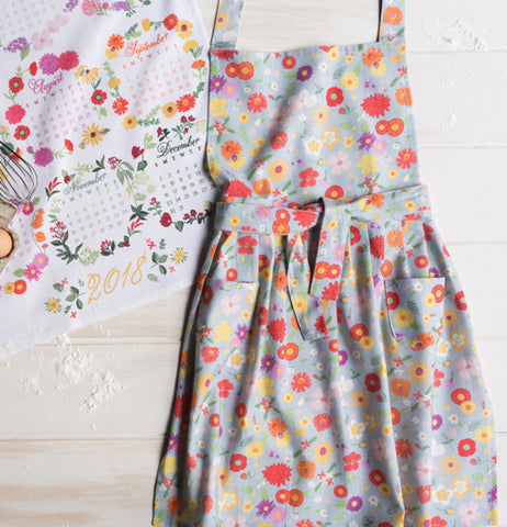 Floral of the Month design apron over a light gray background.