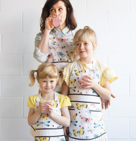 This apron has different insects on a white background.It shows a mom and her kids wearing wearing the Fly Away Sally Apron with the different insects on the apron.