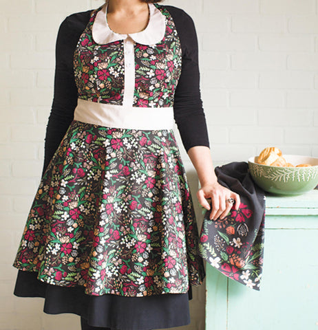 A woman wearing a retro-styled Zoe Apron with a floral print.