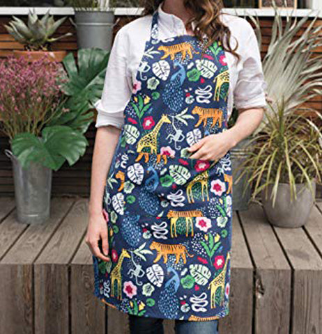 "A woman is wearing a chef ""Wild Bunch"" apron with plants on a wooden bench in the background."