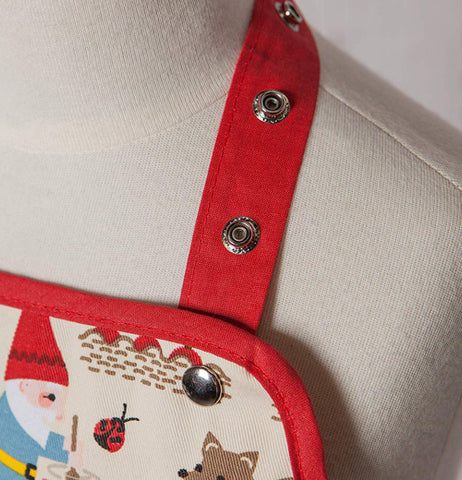 A red strap of a kid's Gnome Sweet Gnome apron has two buttons.
