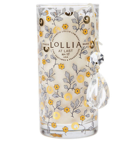 "This candle has yellow flowers with stems and leaves and says ""Authentic Lollia Luminary Fine Perfumes & Fragrances Trade Mark Lillia At Last No. 17 USA."""