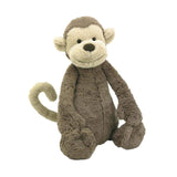 This image shows the Bashful Large stuffed monkey sitting down. It has a light brown colored body and the back of it's head, with the front of its face, ears and tail a cream color.