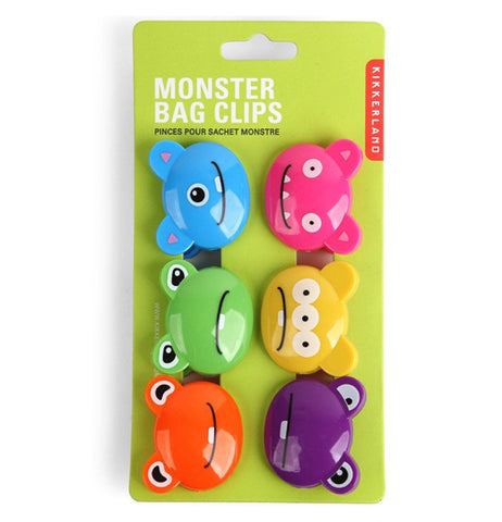 "The different colored monster-shaped clips are shown attached to their green packaging. The words, ""Monster Bag Clips"" are shown above in white lettering."