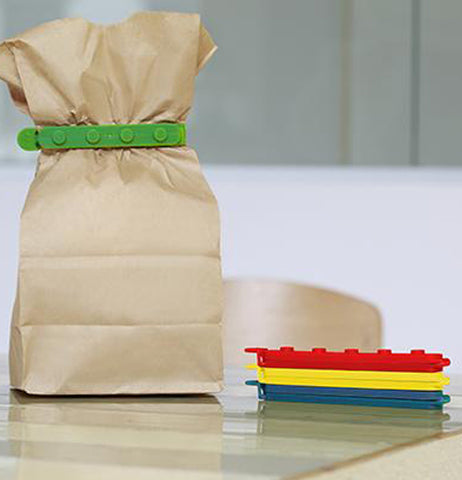 "Three of the ""Stackable Bag Clips"" are on the table with the green one clipping the paper lunch bag closed ."