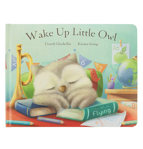 "This book has a front cover depicting a little owl sleeping on top of two books with a trumpet sitting on a red table. Some flags sit behind the owl. At the top of the book is the title, ""Wake Up Little Owl"" and the author's name, ""Kirsten Irving"" in brown lettering."