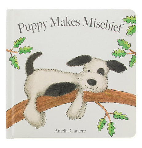 "A white book cover with a black and white spotted puppy laying on a tree branch with the title ""Puppy Makes Mischief"" above"
