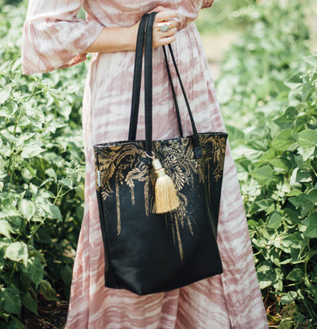"A lady carries the ""Tree of Life"" Tote Bag outside in front of greenery, to show what the bag would look like on a daily wear."