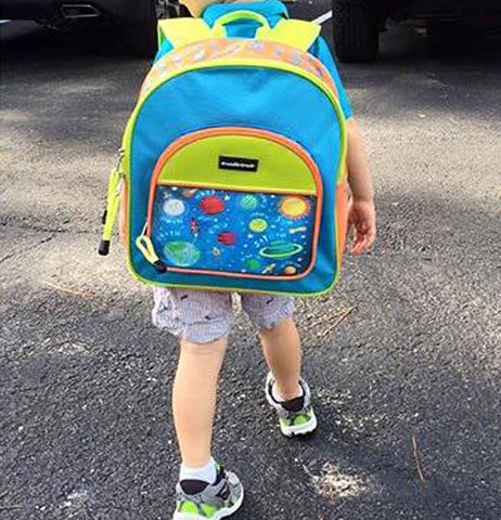A child ready for school wearing the solar system backpack.