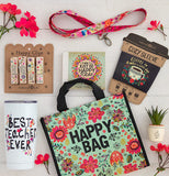 "The ""Teacher"" clips are shown in their packaging next to merchandise that has similar designs, including a tote bag, a drink cozy, a cup, a ribbon, and a small fake plant."
