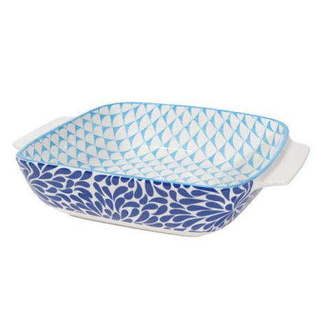 A baking dish with a dark blue, leaf-like design on the outside, and an aqua, triangular design on the inside.