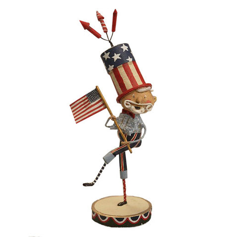 This figurine is of a man with a white beard dressed in light and dark blue holding the American flag and wearing a top hat with an American flag design on it. Three fireworks rockets are shown at the top of the hat.