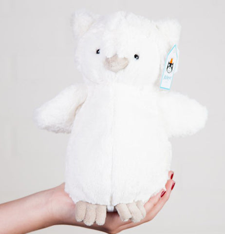 a plush white owl sitting on the hands of a woman.
