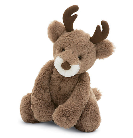 A light brown reindeer with a white muzzle positioned in the sitting position